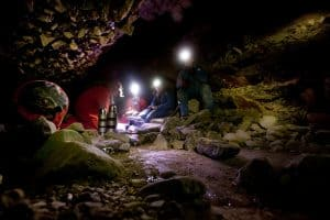 A group of people eating lunch in a dark cave