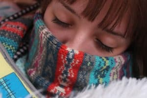 A woman wraps up with a scarf and blankets to avoid the cold