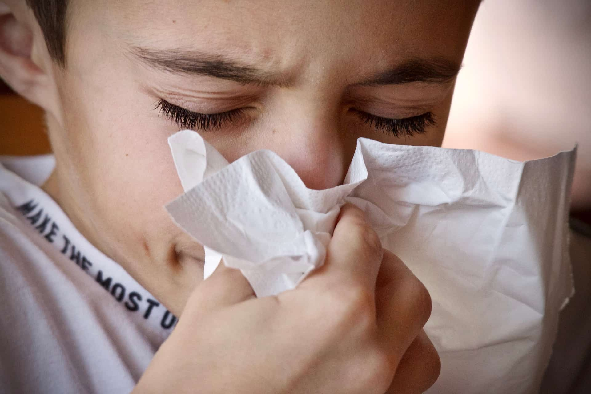 A young girl blows her nose because of allergies